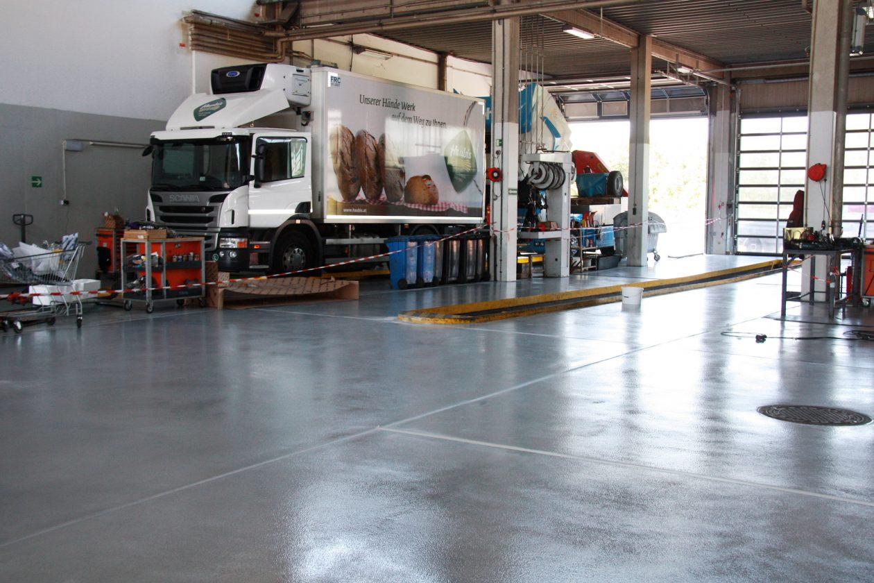 In dieser Werkstatthalle sieht man eine graue, rutschfeste Bodenbeschichtung. Die zum Volkswagenkonzern gehörende Firma Scania repariert gerade einen LKW eines weiteren Kunden von uns.