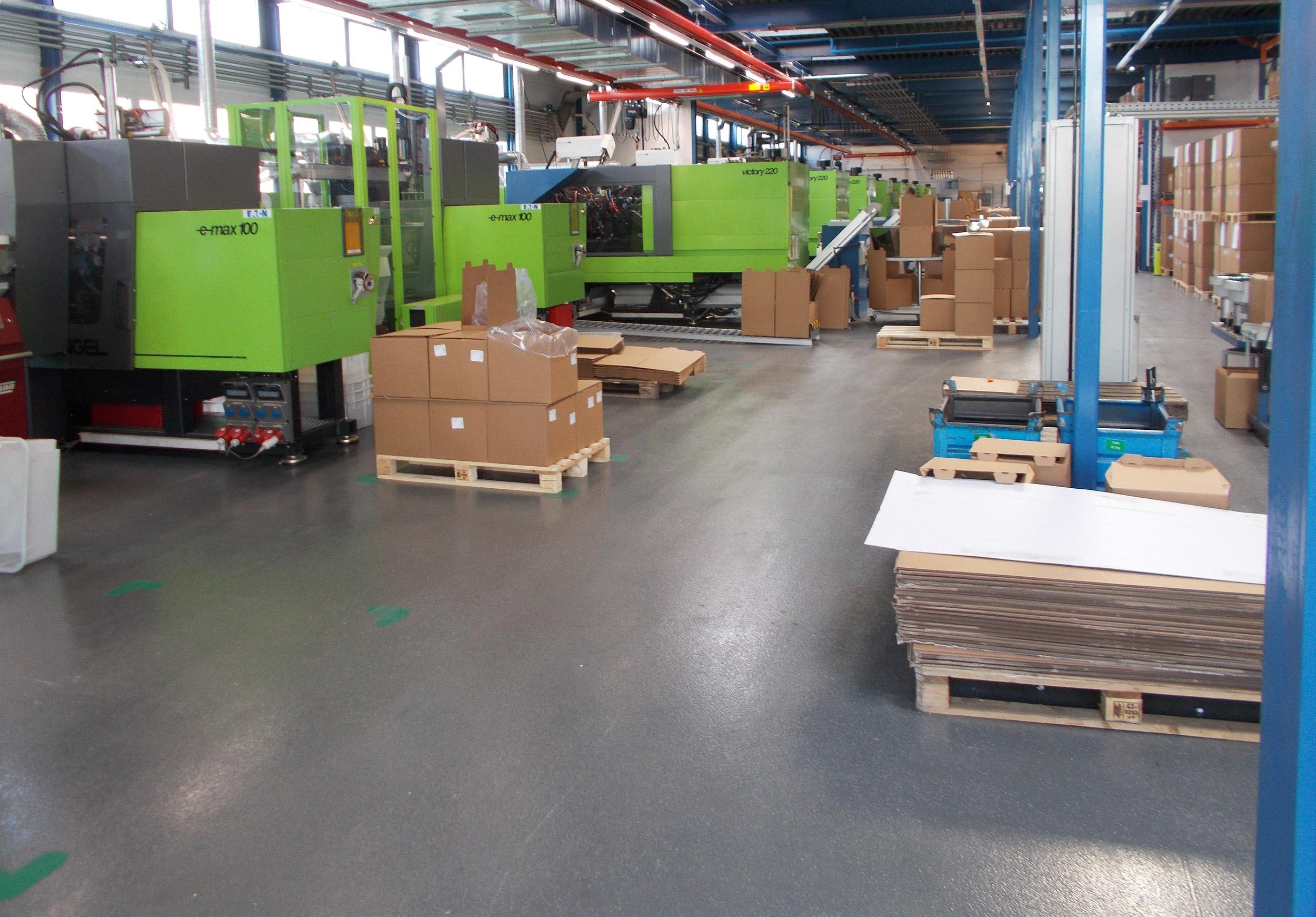 rutschfeste, dunkelgraue Bodenbeschichtung in einer Industriehalle zur Herstellung von Kunststoffspritzteilen