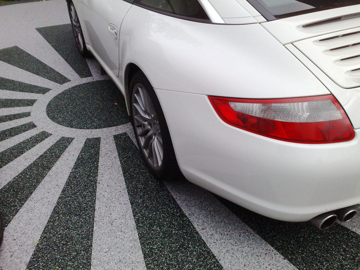 Steinteppich auf Carport mit asiatischer Sonne. Darauf parkt ein Porsche 911 Targa 4s
