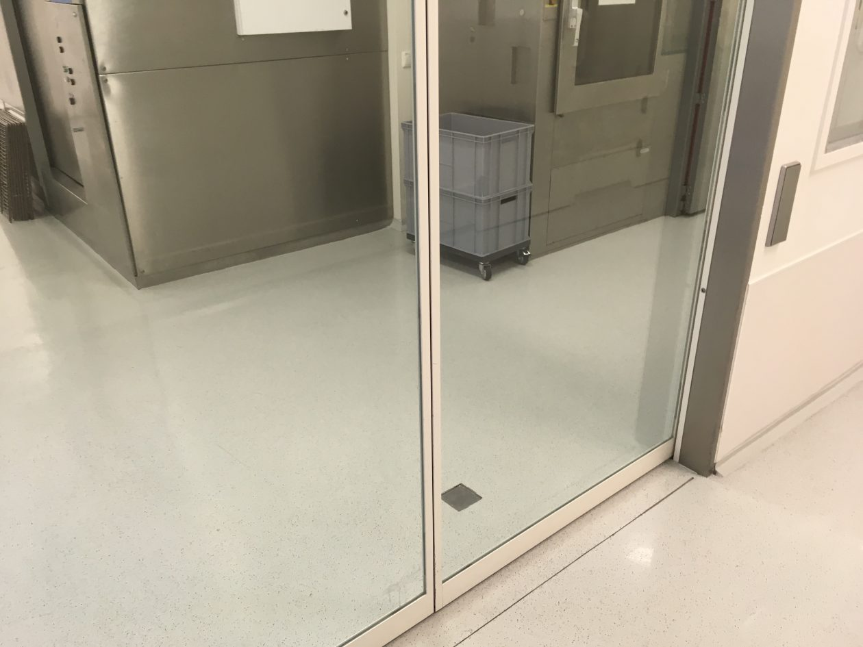 Weiße Bodenbeschichtung mit Glasschiebetür in einem Pharmaunternehmen. die leichte Einstreuung mittels Kunsstoffflocken ist erkennbar.