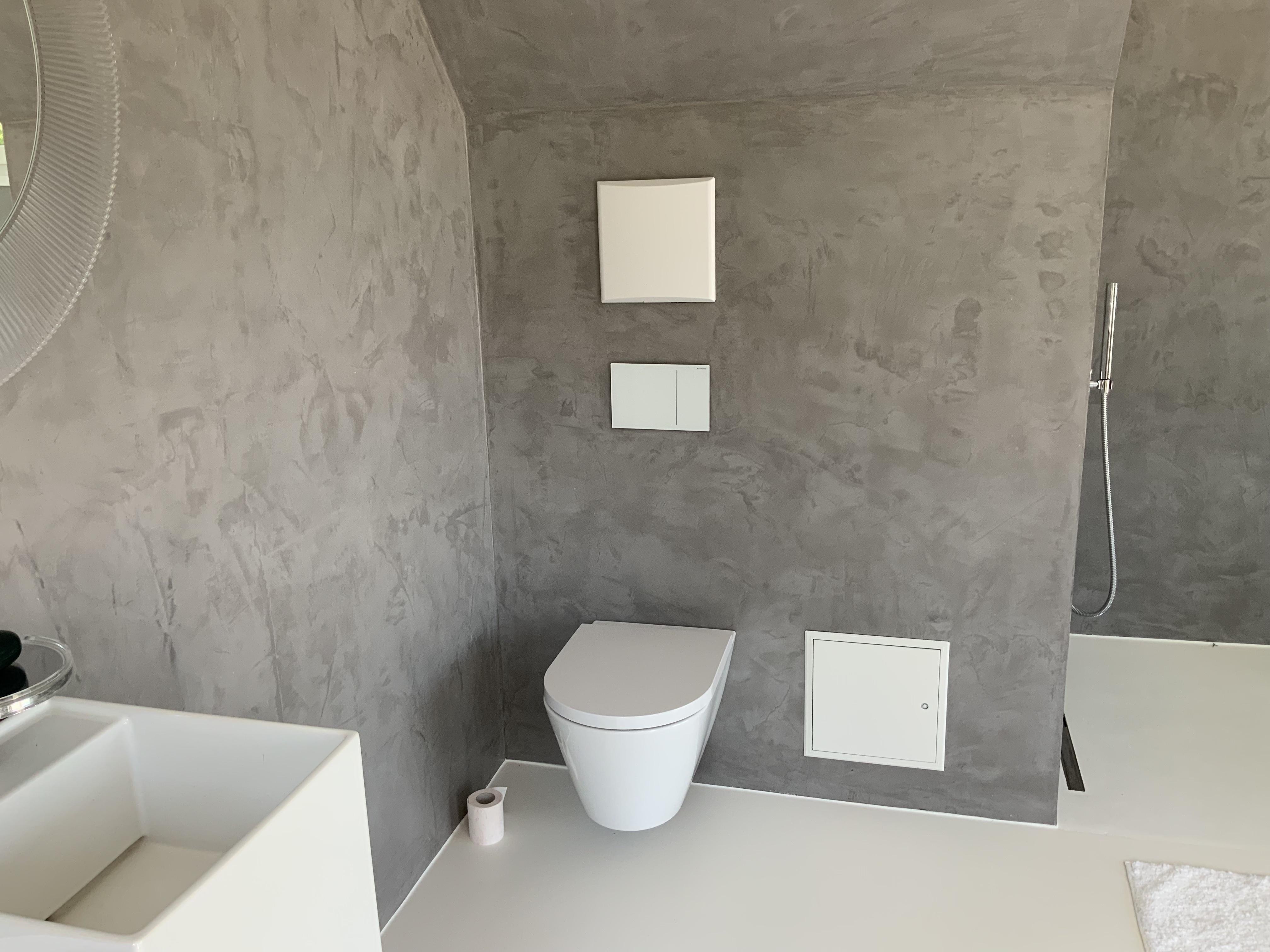 zementäre Wandbeschichtung in Betonoptik in einem Badezimmer mit weißer Bodenbeschichtung