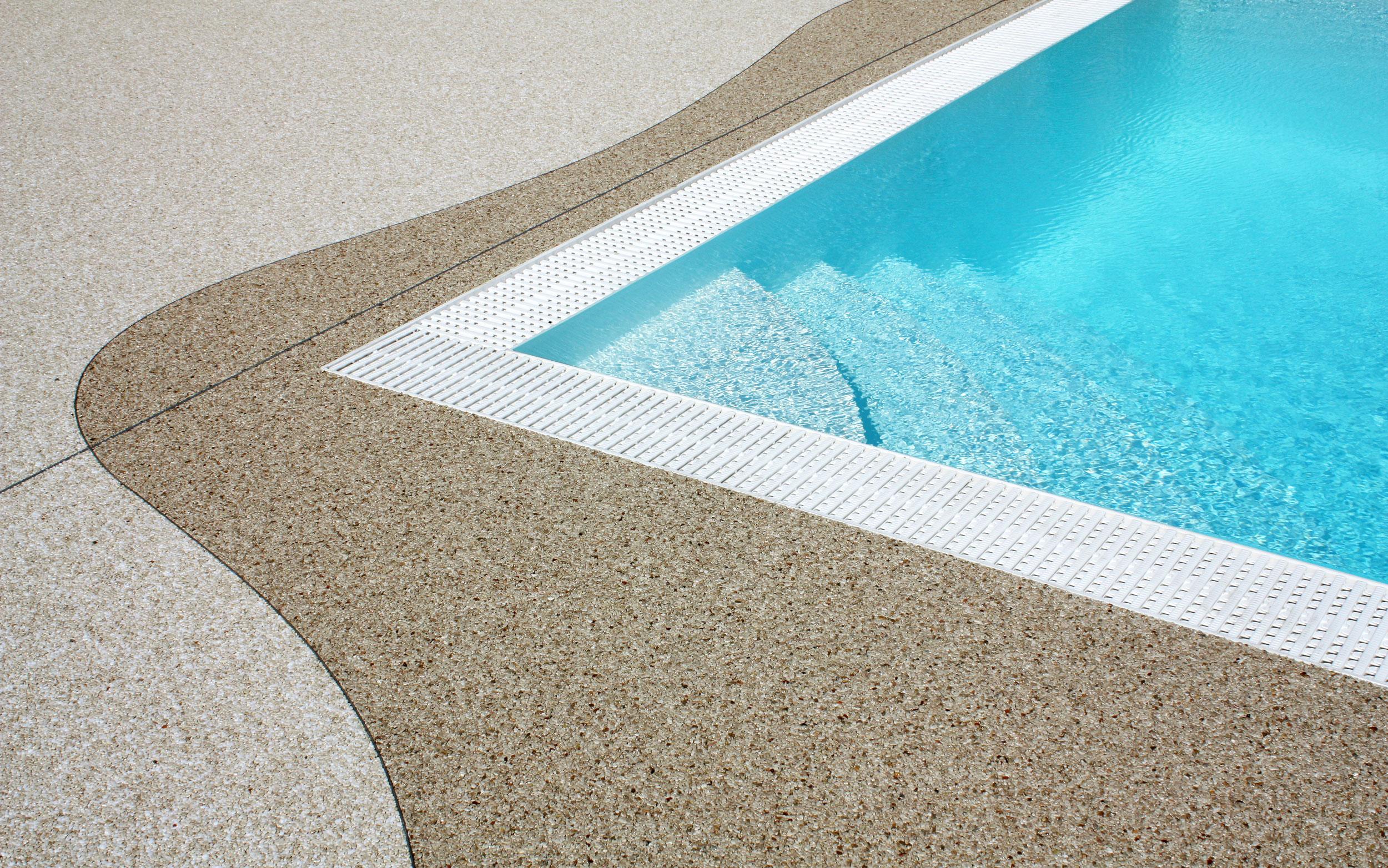 Ein dunkelbeiger Natursteinteppich umrandet mit geschwungener Linie ein Pool mit überlaufrinne. Der restliche Bereich wurde in einem hellern Farbeton verlegt